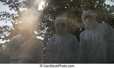Scary team of biohazard engineers workers team dressed in...