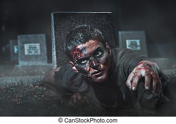 scary zombie crawls out of the grave at the cemetery