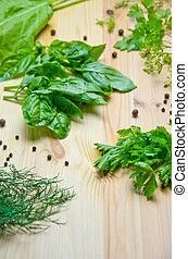 scattered heaps of Basil and lettuce and dill and parsley beside pepper peas on wooden background