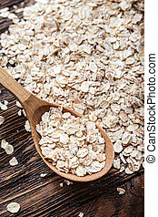 Scattered oatmeal on a wooden table in a wooden spoon. Healthy food for breakfast. Space for text