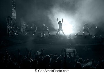 Scene from rock concert - Concert: silhouette of rock singer...