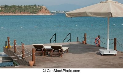Scene of a summer day near the sea with wooden bathing platform ready for relax with unoccupied sunbeds and umbrella with bay and sea on the background. 4k.