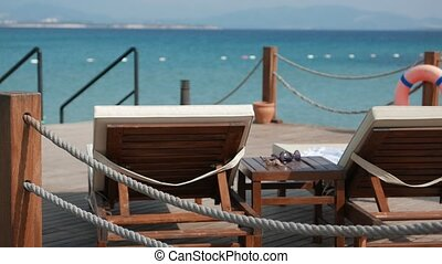 Scene of a sunny day with empty wooden deck chairs and coffee table with a sunglasses and shells with sea on the background. 4k.