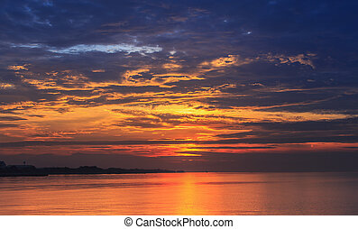 Scene of golden hour sky with dark cloud reflecting on flat water surface with orange light before sunrise.