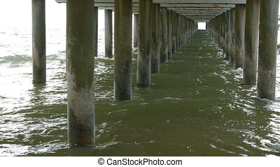 Scene of under the old concrete jetty with sea shore and sky