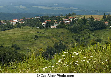 Scene with mountain glade, forest and residential district of bulgarian village Plana
