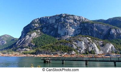 Scenery rocky mountains trees ocean landscape pan shot