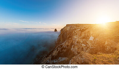 Scenery with shining sun in the sky over the misty Sea coast at sunset. Clouds and fog over the rocky seashore. Silhouette of cliff. Copy space. The concept of calmness, silence and unity with nature.
