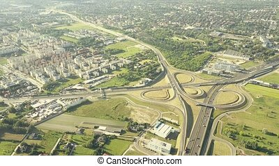 Scenic aerial shot of modern highway interchange in outskirts of a big city on a sunny summer day