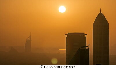 Scenic aerial view of a big modern city with sunset timelapse. Business bay, Dubai, United Arab Emirates.