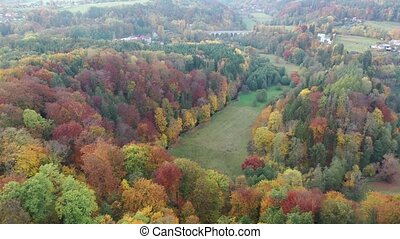 Picturesque view of country landscape with colorful trees on hillsides in autumn day