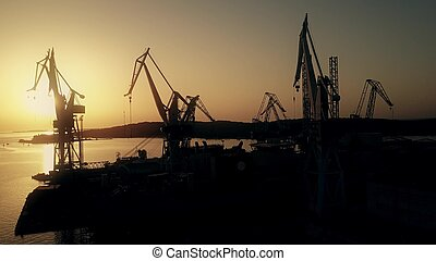 Scenic aerial view of the shipyard cranes and the sea harbour at sunset