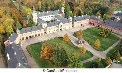 Scenic autumn landscape with large Castle complex near village of Sychrov with romantic neogothic building and English style park, Czech Republic