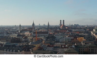 Scenic Cityscape of Munich, Germany Aerial Dolly right with Sun reflection of Construction Site Crane, Drone sideways flight 4K