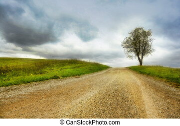 scenic country road with single tree and heavy clouds