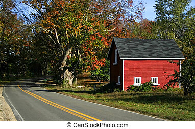 Red barn and colorful trees by the road