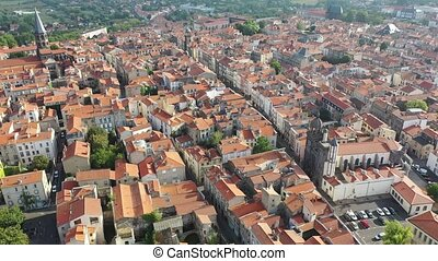 Aerial view of residential area of Riom town with similar brownish roofs in summer, Auvergne, France