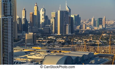 Scenic Dubai downtown skyline timelapse at sunset time. Rooftop view of Sheikh Zayed road with numerous illuminated towers.
