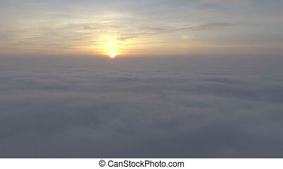 Scenic flight above the clouds towards the sun.