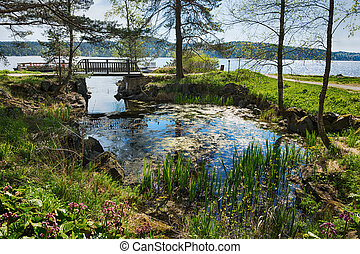 Scenic landscape with a bridge in a park on the shore of a lake in Karelia