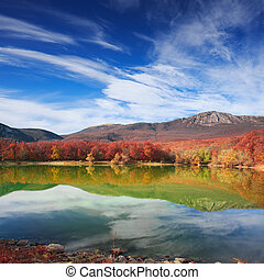 Scenic mountain lake with autumnal forest along the shore and blue cloudy sky above and in the reflection in water surface
