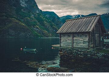 Scenic Norwegian Fjord Landscape with Rustic Cabin