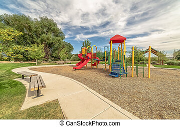 Scenic park and colorful playground under blue sky and clouds on a sunny day