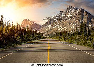 Scenic road in the Canadian Rockies during a vibrant sunny summer sunrise. Sky Composite. Taken in Icefields Parkway, Banff National Park, Alberta, Canada.