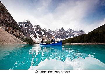 Man and woman sailing on peaceful lake against mountain range