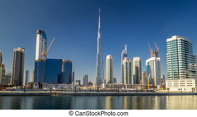 Scenic skyline of Dubai's business bay with skyscrapers at day time timelapse hyperlapse with blue sky and reflection in water