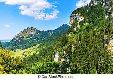 Scenic summer landscape with Alps mountains, hills and green field or meadow and forest in Bavaria, Germany, Central Europe