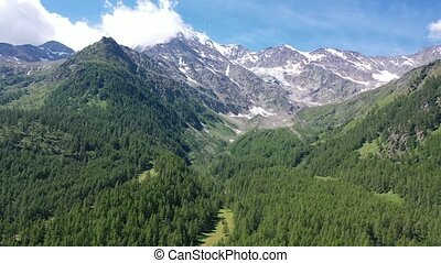 Unique summer Alpine landscape seen from Simplon Pass with rocky mountain ranges and greenery on foothills in Switzerland