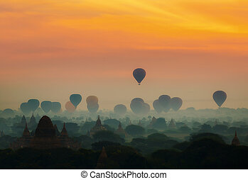 cenic sunrise with many hot air balloons above Bagan in Myanmar