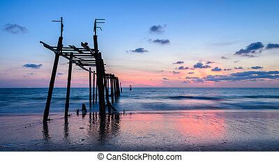 Scenic sunset beach with abandoned wooden pier