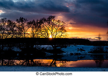 Scenic sunset over the trees above the river