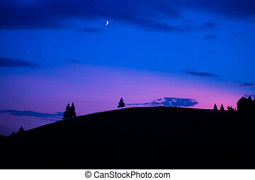Scenic sunset with moon rise over mountain silhouette