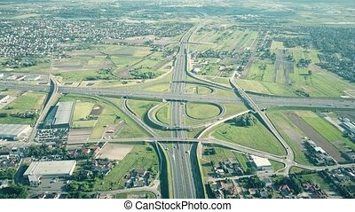 Scenic travelling aerial shot of big highway interchange in outskirts on a sunny summer day