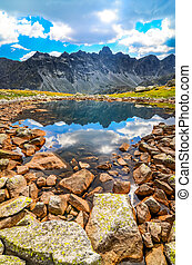 scenic vertical view of a mountain lake and rocks in High Tatras, Slovakia