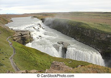 Scenic view from above on Iceland's Gulfoss waterfall with people walking down the hikeway along the canyon