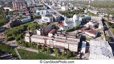 Aerial view of architectural ensemble of monastery of Our Lady of Kursk with Znamensky Cathedral on background of modern cityscape, Russia