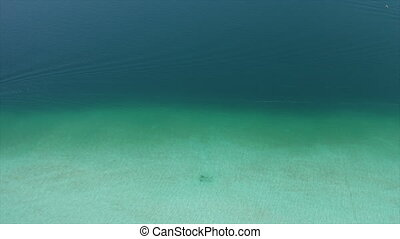 4k aerial drone shot over the shallow crystal clear water around the docks towards the blue dense water off the coast in the Lake, Mexico