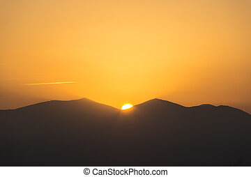 Scenic view of a beautiful rich orange sunset over the black silhouettes of the mountains