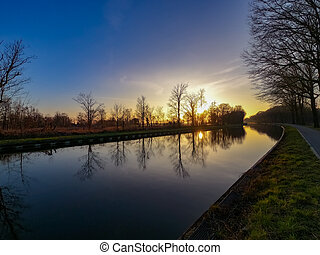 Scenic view of a beautiful sunset over the river in spring against the background of the blue and golden sky, the sun over the water and silhouettes of bare trees in the foreground.