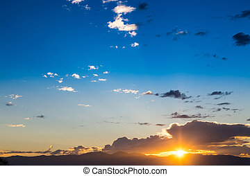 Scenic view of a beautiful sunset with blue sky and clouds over the mountains
