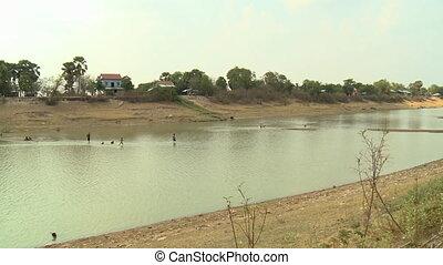 Scenic view of a lake with kids running in water - A long...