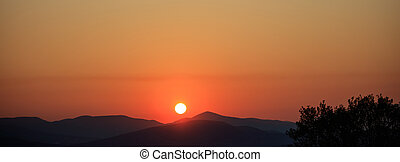 Scenic view of an orange sunset over the mountains
