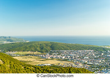 Scenic view of Black sea coastline, green forest areas, grass fields in the lowland and cityscape of Gelendzhik resort in Russia. Residential houses.