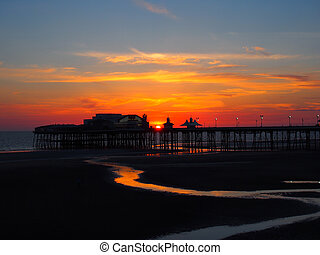 scenic view of blackpool north pier in glowing red evening light at sunset with illuminated pink and yellow sky and clouds with colours reflected on the dark beach in structure in silhouette