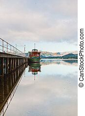 Scenic view of boats moored by wooden pier , Lake District National Park, England.