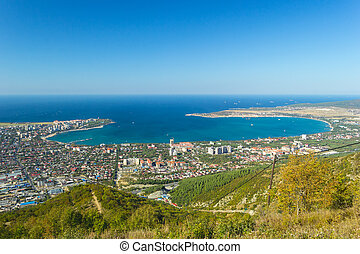Scenic view of Gelendzhik city and sea bay. Sunny day. Trees on hills on foreground. Photo of popular resort from hill of caucasian mountains.